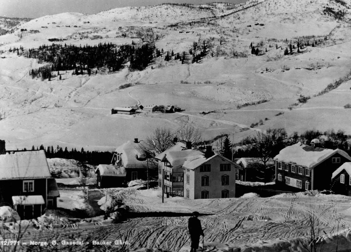 Avfotografert postkort. En mannlig skiløper foran Bauker gård, Østre Gausdal. Snødekt fjell- og skogslandskap i bakgrunnen.