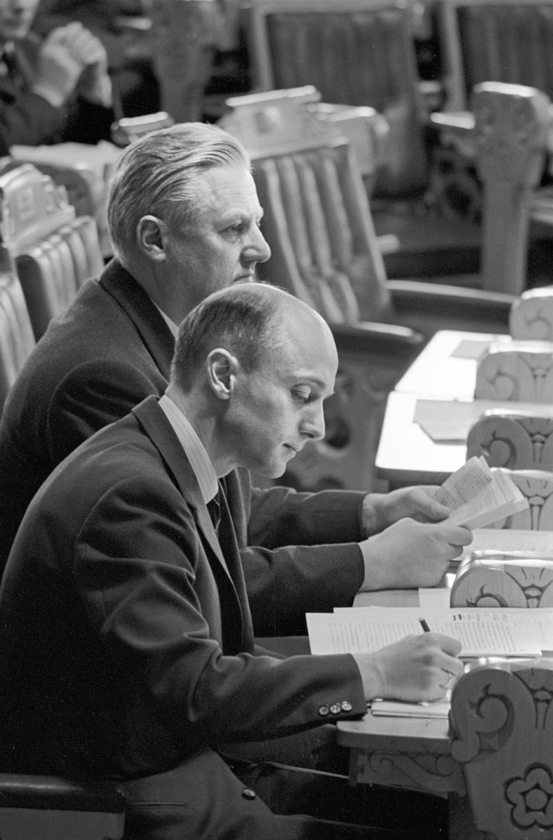 Serie. Debatt i Stortinget. Kåre Willoch og John Lyng leser dokumenter og en kvinne snakker med en politiker. Fotografert våren 1967.