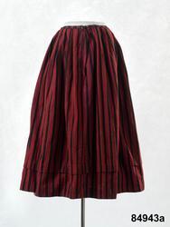 Kvinnodräkt a-c.  a. Kjol av ylletyg, svart botten med röda och gröna ränder. b. Livstycke av äldre typ med skört och snörning. Av halvylle, rött med smala ränder i mörkare rött, grönt, vitt och en tråd svart i varje grön rand,varp av mörkgrått lingarn, inslag i korskypert helt täckande varpen. 2 framstycken/sidstycken med svängt sprund fram i nederkant och 3 rundade skörtflikar bak, 2 ryggstycken som avsmalnar nedåt i rundade skörtflikar, sammanlagt har skörtet 8 rundade skörtflikar som överlappar varandra som fjäll. Snörning med 7 par snörhål kantsydda med grågrönt lingarn. Foder av kraftig blekt linnelärft. Anm. Små vävfel i halvylletyget. Små malhål på ett par ställen. Livstycket mönsterritat av E. Liljedahl-Persson. /Berit Eldvik 2008-02-22 c. Tröja av halvylletyg, mörkröd botten med smala ljusare röda, gröna, vita och svarta ränder. Ärmarna skurna i ett med bålen. Tröjan består av 2 stycken med tre sömmar i ryggen och söm under ärmen. Breda infällda skörtkilar i sidorna. Bak är två rektangulära bitar iskarvade för ryggskörtet som har tre veck. Ovanför skörtvecken 2 små flata tygklädda knappar. Framstyckena har en tillskarvad bit i nederkanten som är lätt rundad. Raka framkanter utan knäppning. Foder av grov halvblekt linne- eller hamplärft. /Berit Eldvik 2008-10-01