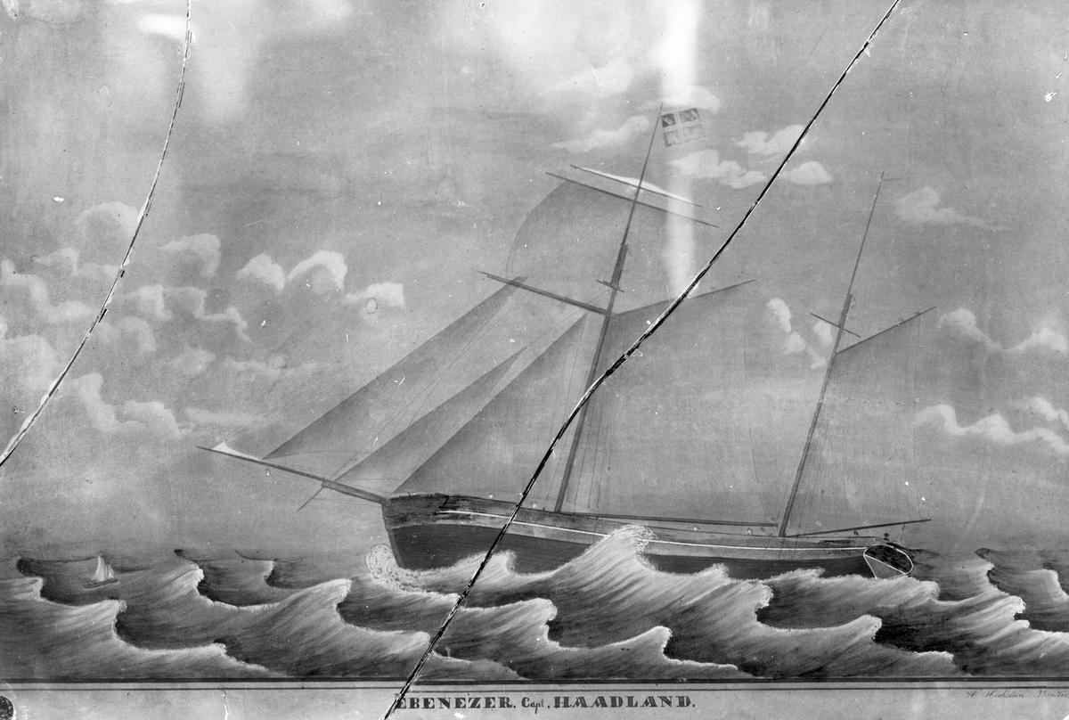 """Avfotografert maleri av Galeasen """"Ebenezer"""" i store bølger. En liten robåt ligger på siden av akterenden. Glassplata er knust."""