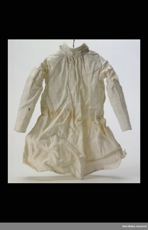 Inventering Sesam 1996-1999: a)  L  26  cm b)  L  31  cm 2 st skjortor av linne. lång ärm och krage.  Tillhör docka inv 108.264.  Birgitta Martinius 1996