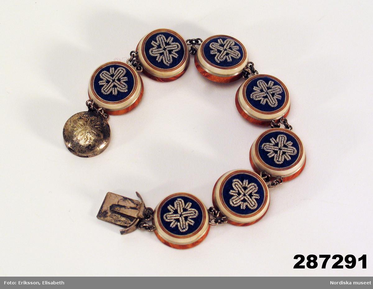 """Huvudliggaren: """"Armband av masurbjörk och horn; 7 runda brickor, Diam 2,3 cm; kanten med infälld tennrand; ovansidan med tenntrådsornering på blått kläde; runt silverspänne med ornering; stpl 'BÅ-stadsstpl. 3 kr-S-U9'; inristat 'EM-NI'. L 24 cm. Tillv. av säljaren. I[nköpt] 14/3 1973 [från] Ellen Margareta Nutti, Gällivare [...]. [Brukningsort:] Lappland Gällivare sn."""""""