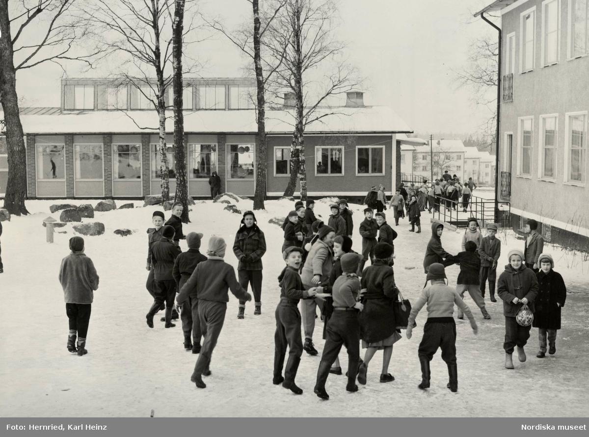 Skola i Borås, Västergötland. Exteriör med skolbyggnad och elever ute i snö.