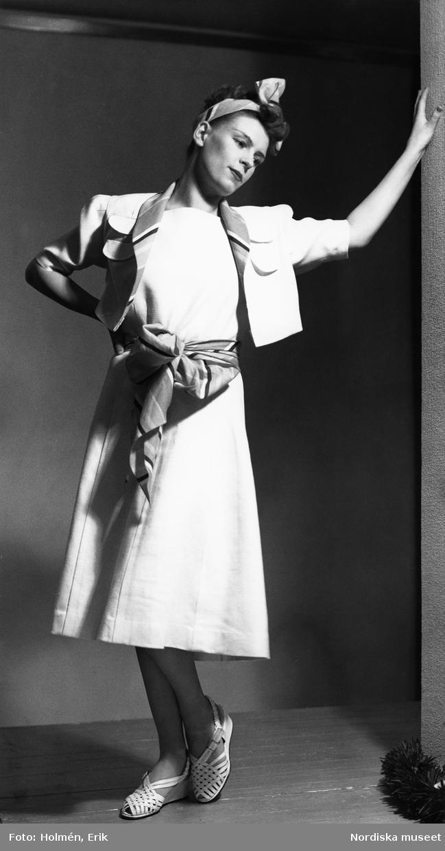 Modell i vit klänning och kort jacka. Mönstrat skärp och sjal i håret, vita sandaletter.