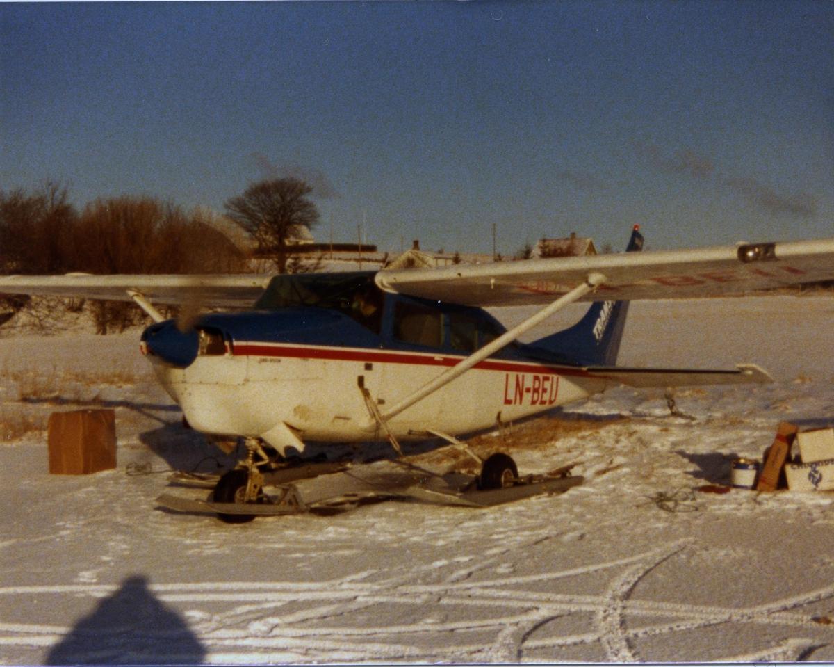 Lufthavn (flyplass). Ett fly, LN-BEU, Cessna 206, fra Bergen Ait Transport, Utstyrt med hjul og ski. Snødekke.