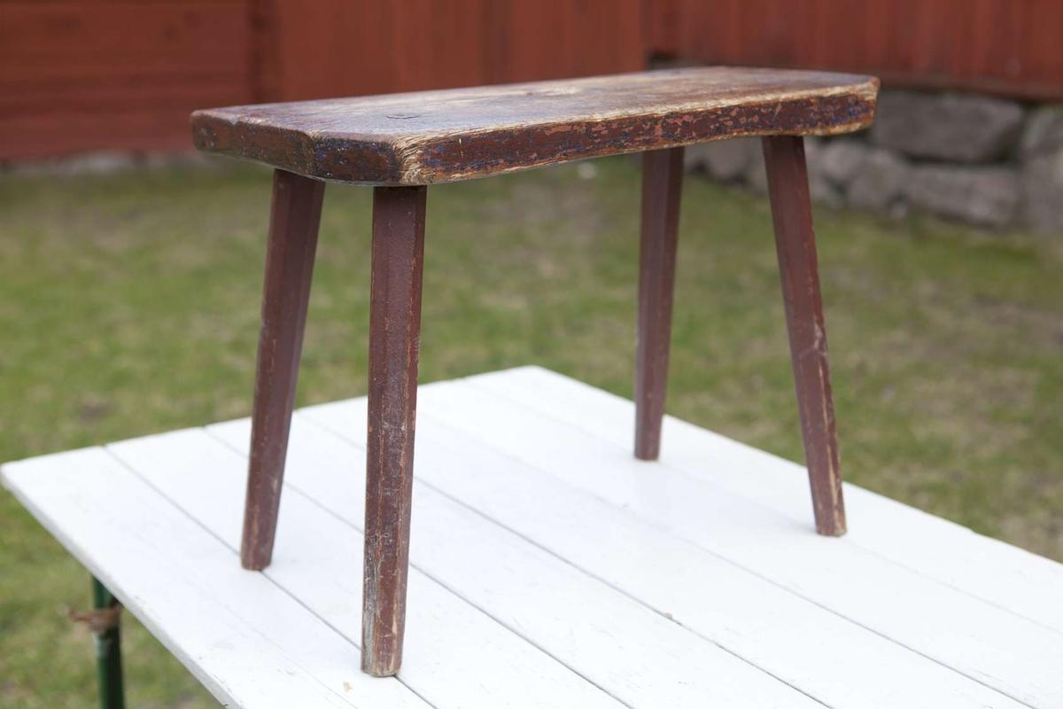 Pall av trä. Sits av hel ekplanka med runt grepphål, fyra åttkantiga itappade ben. Målad mörkt brunröd, därunder finns ett blått lager och troligen därunder även ett brunt.