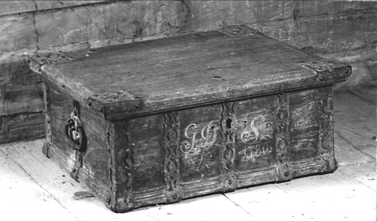 Kista av trä. Målad i mörkbrunt. Märkt omkring låset med vitt: GDS A 1780. Genombrutna järnbeslag. Bärringar på kortsidorna.