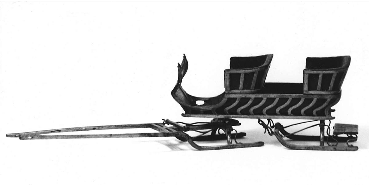 Leksak, släde av trä. Främre medparet ledat, löstagbart. Vagnskorg av svängda ribbor och svart läder. Löstagbara säten, läderskärm framtill.