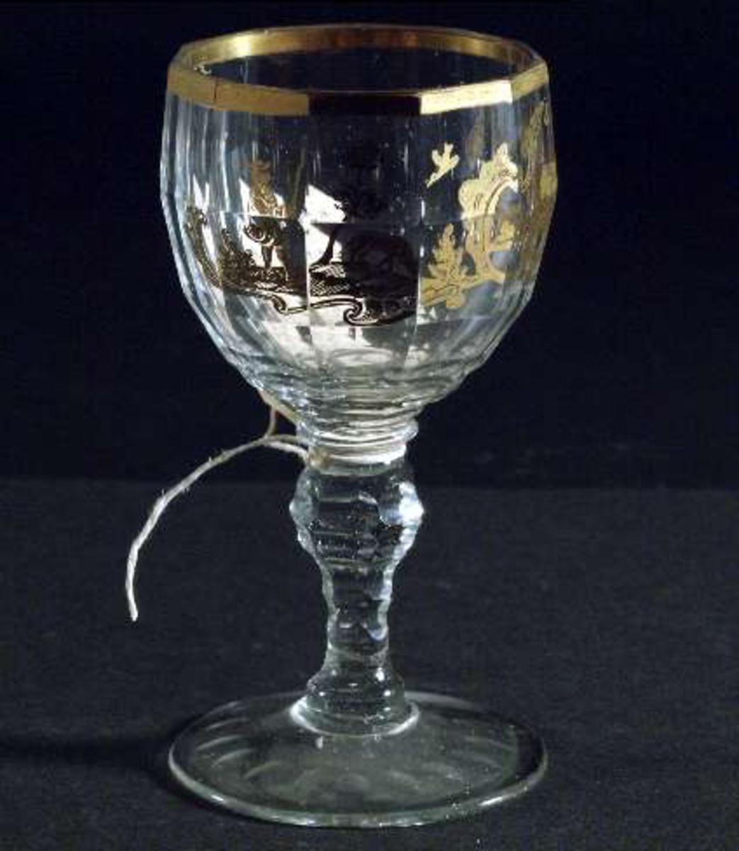 Vinglas av ofärgat något småblåsigt glas med fasettslipad kupa, guldkant upptill på kupan samt gulddekor i rokokostil, foten på undersidan olivslipad. Puntelmärke på fotens undersida.