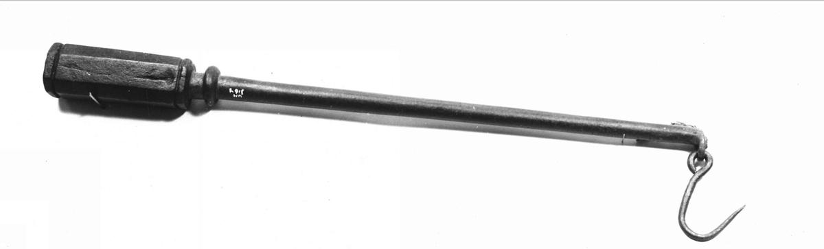 """Besman helt av järn med fyrsidig tyngd med avfasade hörn och profilerade ytterändar. I stången finns en lång rad hål inslagna. Tyngden bär texten: """"IE 1620""""."""