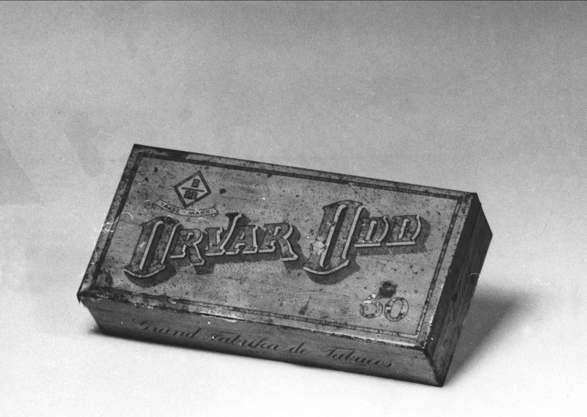 """Ask av järnplåt. Gul med träimitation. Text på locket: """"Trade-mark, Orvar Odd, 50"""". På framsidan: """"Grand Fabrika de Tabacos""""."""