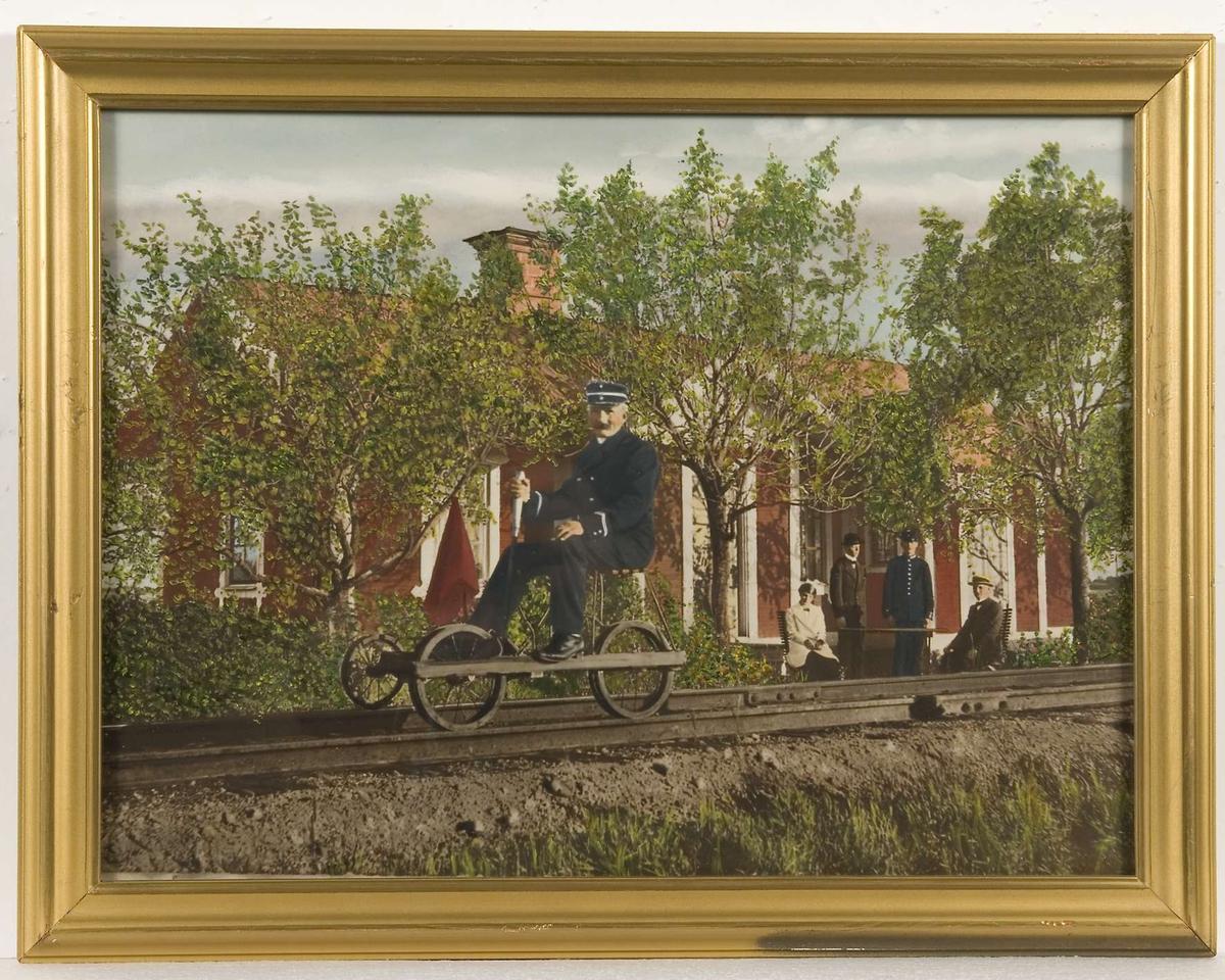 I förgrunden ett järnvägsspår, en stins sitter på en dressin. I bakgrunden en byggnad målad i rött med vita snickerier. Tre män och en kvinna befinner sig framför huset. Bilden färglagd i grönt, blått, rött och vitt.
