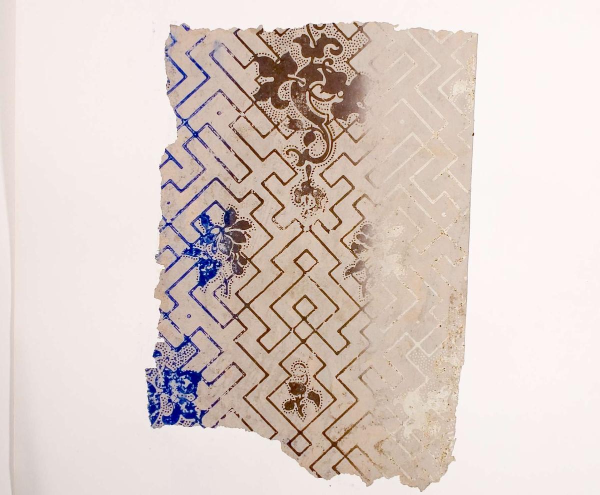 Tapetprov med tryckt mönster i grått, blått och brunt.