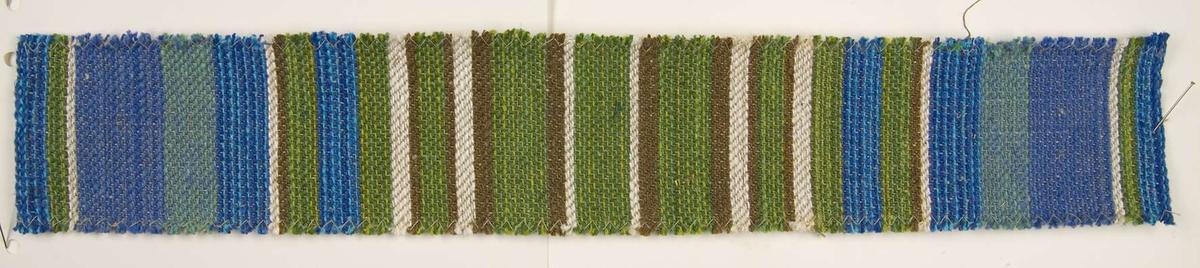 """Vävprov av löpare, randig i grönt, blått, vitt och brunt. Löparen är vävd i kypert av linbogarn och lingarn. Vävprovet är fastsytt vid ett tjockt papper. Till vävprovet hör en vävsedel med information om löparen. På vävsedeln står bland annat """"Löpare 'Trollslända' Komp. A.M. Wiktorsson""""."""