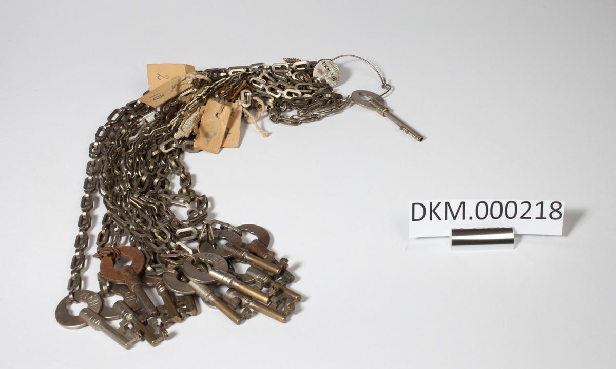 Knippe med 13 nøkler i stålkjettinger. Det er også festet flere papirlapper med tråd til kjettingene.