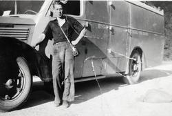 """Sjåfør Gustav Hårtveit klar til avgang fra Byremo. Bilen er en Dodge, årsmodell 1937-38. (Jfr. bokstavene """"DGE"""" på siden av panseret.)"""
