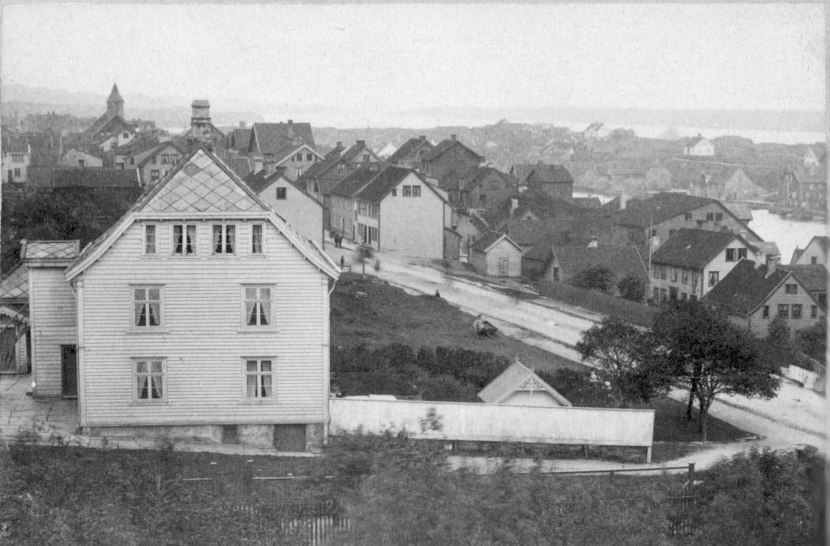 Christiansenshuset. Bildet er tatt fra nord og ser sørover Strandgt. Bebyggelsen på Risøy er ennå nokså spredt, dette er før det bygges konsentrert boligbebyggelse på Risøy. Til v. i bildet et stort klassisistisk hus med valmet tak. Foran huset, til h. i bildet ses et hagegjerde og i hagen et lyshus. Nedenfor huset ligger en nokså bred gate med tett bebyggelse på h. side, lenger inn i bildet på begge sider. Utenfor skimtes et sund og en øy med rel. spredt bebyggelse. I bakgrunnen ses et tårnet på det gamle rådhuset.