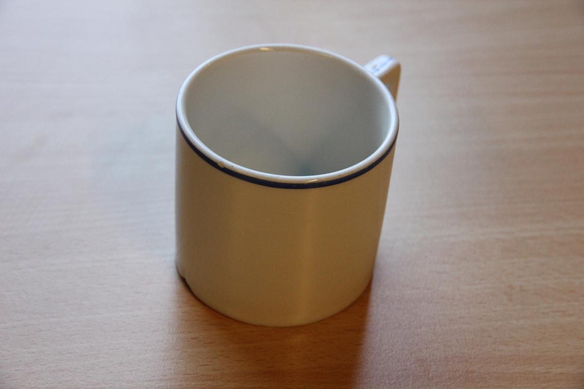 Hvit kopp med blå rand og kantete håndtak.