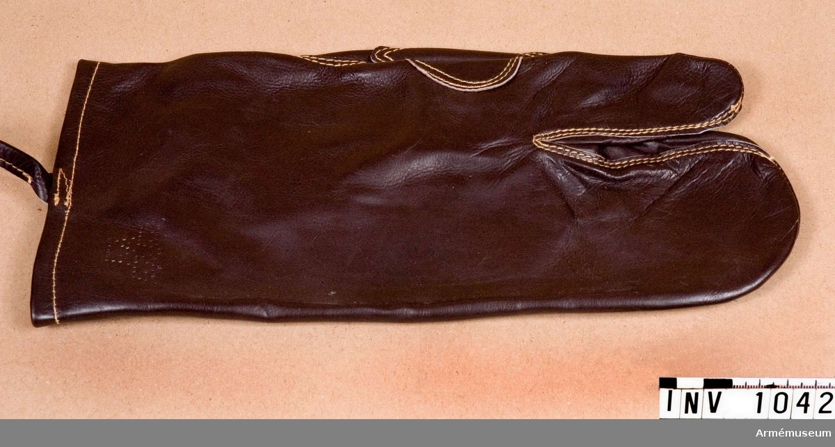 Höger, t uniform 1942 kv. Trefingrad ytterhandske av brunt läder. Avsedd för skjutning. Tumme och pekfinger har var sitt handskfinger, de övriga samma. Skinnet blanka sida är utåt. Dubbelt laskade sömmar och en extra förstärkning av skinn i handflatan. Spännrem vid handleden med tamp av läder och spänne av svart- målad metall. (För att ej blänka och röja bäraren för fienden.) Försedd med trekronorsmärket stämplat i skinnet på framsidan av handsken. Har tillhört mobiliseringsutrustning vid Armémuseum.
