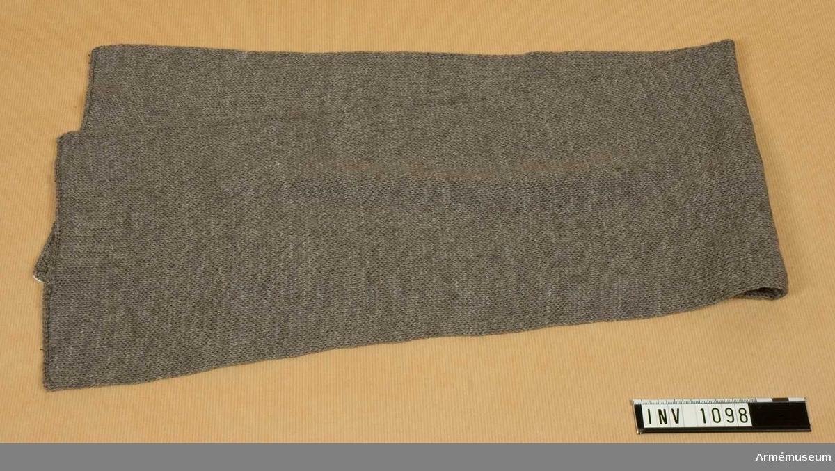 Rundstickad av gråbrungrönt yllegarn. Maskinstickad. Sidorna hopkastade på maskin. Genom att vika in en kortsida mot avigsidan kan man trä halsduken som en mössa på huvudet.