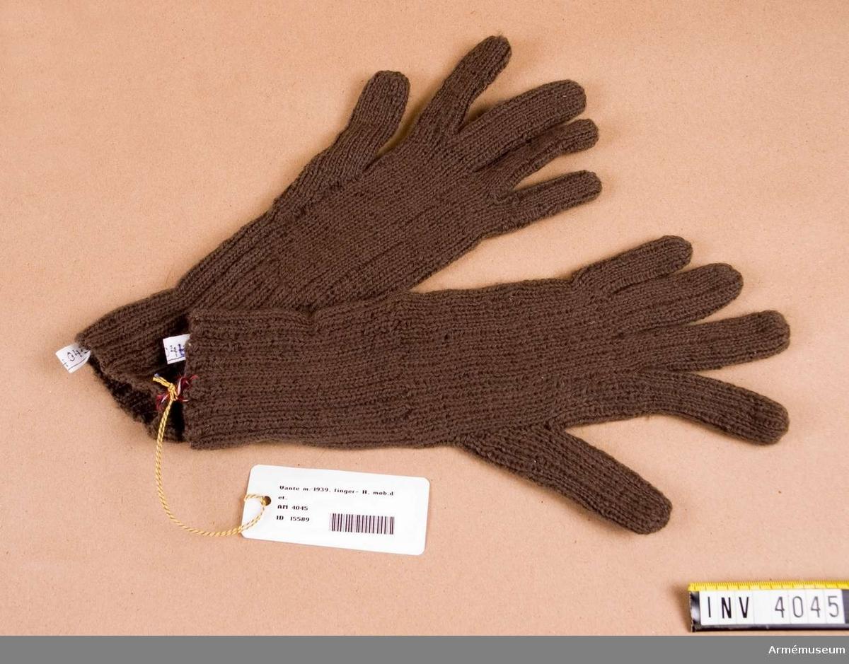 Vante m/1939, H.Av gråbrungrönt yllegarn och stickad med alla fingrar fria.  Har tillhört rustmästare O Skoogs mobutrustning på AM.