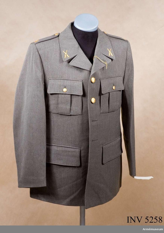 Skick som ny. Storlek: 100 U. Av samma snitt som uniform m/1939. Daglig dräkt av gråbrungrönt tyg. Bärs till mörkt gråbrungröna byxor. Tjänstetecken mattförgyllda.