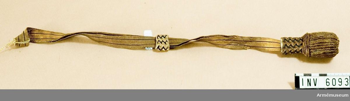 Samhörande nr är 5828-5899, 6000-6099, 6200-6212. Av guldgalonband, taget dubbelt med sölja av gulddrageriarbete och svart silke. Tofs av gulddrageri m vävd ståndare av guld och svart silke. Fastsättes på sabel m/1899, i fästets nedre del.