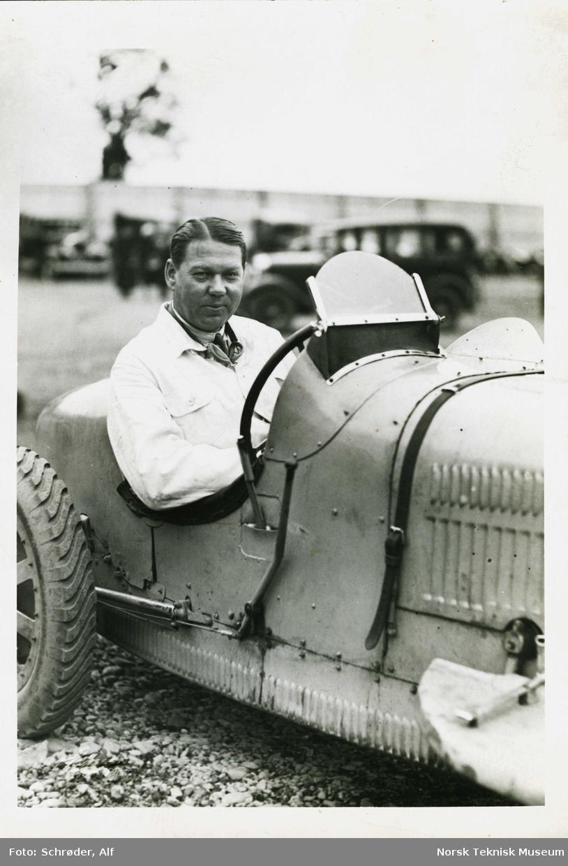 John Erik Isberg med hvit jakke bak rattet på sin Bugatti.