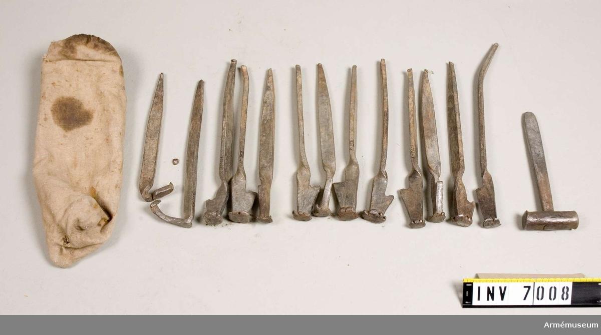 400 mm långa. Förutom tältpinnarna finns en hammare med i denna linnepåse. Hammaren är av järn.   Samhörande nr är AM.7006-11