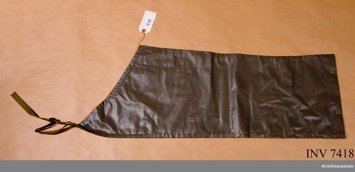 Skyddsbyxben fm/1955. Av grågrön plastbelagd väv med nedtill i fållen fyra  öljetterade hål och upptill fasonerad med ett öljetterat hål i innersömmens fåll och med på högsta punkt i yttersömmen ett grönt textilband med spänne. Färg grågrön P.