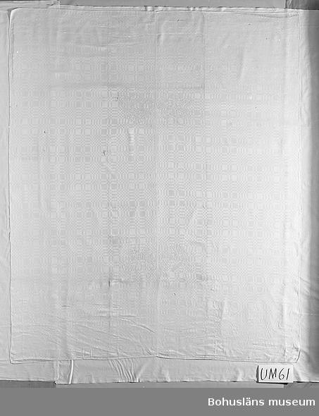"""Vit drällduk vävd i 5-skafts satin, dvs i en vävstol där tio skaft behövs för att få fram skiftningen mellan varp- och inslagseffekt. Rutmönstrad. Märkt med Thomas Dyres och hans hustru Margareta Huitfeldts vapen samt årtal broderat i variant av flätsöm? el. kedjestygn? med vit lintråd: """"TD MHF 1651"""" (HF är sammanskrivet). Vapnen är vapensköldar med omgivande """"gardiner"""" och upptill riddarhjälmar, med vimplar på MHF:s vapen och en hornliknande form upptill på TD:s vapen. 1651 var samma år som Thomas Dyre blev sjuk och dog i september. (Losman). Giftermålet hade ägt rum i mars 1635 i Viborg, Jylland.  Tvättad på Historiska museet 1979. Sliten. Bitvis skör. Några hål/bristningar. Flera lagningar, en med infälld dräll-lapp, andra stoppningar. Mörknad, speciellt vid vapnen.  Ur handskrivna katalogen 1957-1958: Drällbordduk  se bilaga Mått: 208 x 175 cm; Margareta Hvitfeldts och Tomas Dyres vapen """"1651""""; lagad på ett par ställen."""