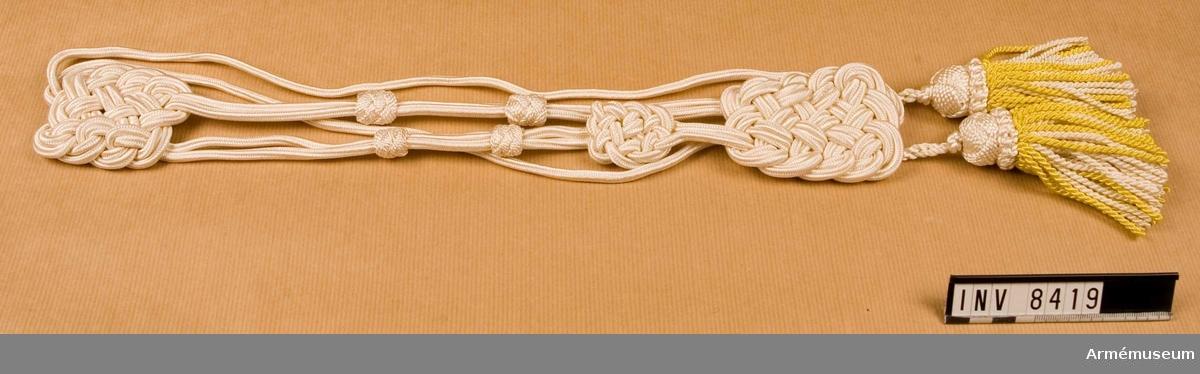 Av vit silkessnodd och gult silke i tofsens yttre skikt, med vitt silke i dess inre. Källa: UNI:A 1977 mom 501 och 502. Tillhör utrustning för  musikavdelningar och vakter.