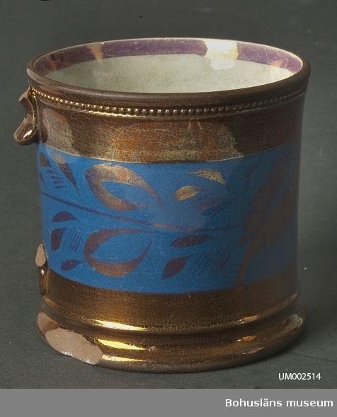 Cylindriskt kärl. Muggen är täckt med kopparlyster och har ett blått, brett fält runt livet. I det blå fältet är det en handmålad dekor i form av blad i kopparlyster. Dekoren ligger under glasyren. Vid mynningen, på utsidan, är det en pärllist. På mynningens insida är det en rand med rosa lyster. Hänkel saknas.  Ur handskrivna katalogen 1957-1958: Mugg, porslin, handtag. def. Bottendiam.: 10,4. H: 10,2. Bronserad och blåfärgad. Handtag saknas. Något skadad i botten; eljest hel.  Lappkatalog: 62