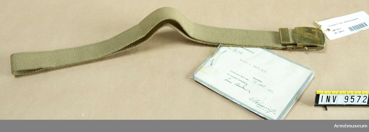 Av ljusgrönt textilband med gulmetallspänne.  Gåva från FMV i Solna.
