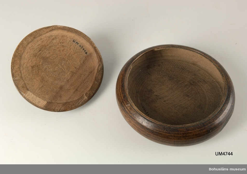 """Rund, svarvad med """"dubbelt"""" lock. Locket har rektangulär knopp. Locken låses med en vridanordning. När två uddsnitt är i linje med varandra är de öppningsbara. Under botten är texten; """"ANSNoby 1821"""" inskuret. Betsad.  Ur handskrivna katalogen 1957-1958: Dosa av trä, dubbellock """"ANSNoby 1821"""" Tre delar a-c; a) Största D. c:a 18; H. 5 cm; b) största D. 15 cm; c) största D. 8,8 cm; Svarvad. Hel.  Litt.; Nylén, Anna-Maja, Hemslöjd, Håkan Ohlssons förlag, Lund, 1978, s. 345-349"""