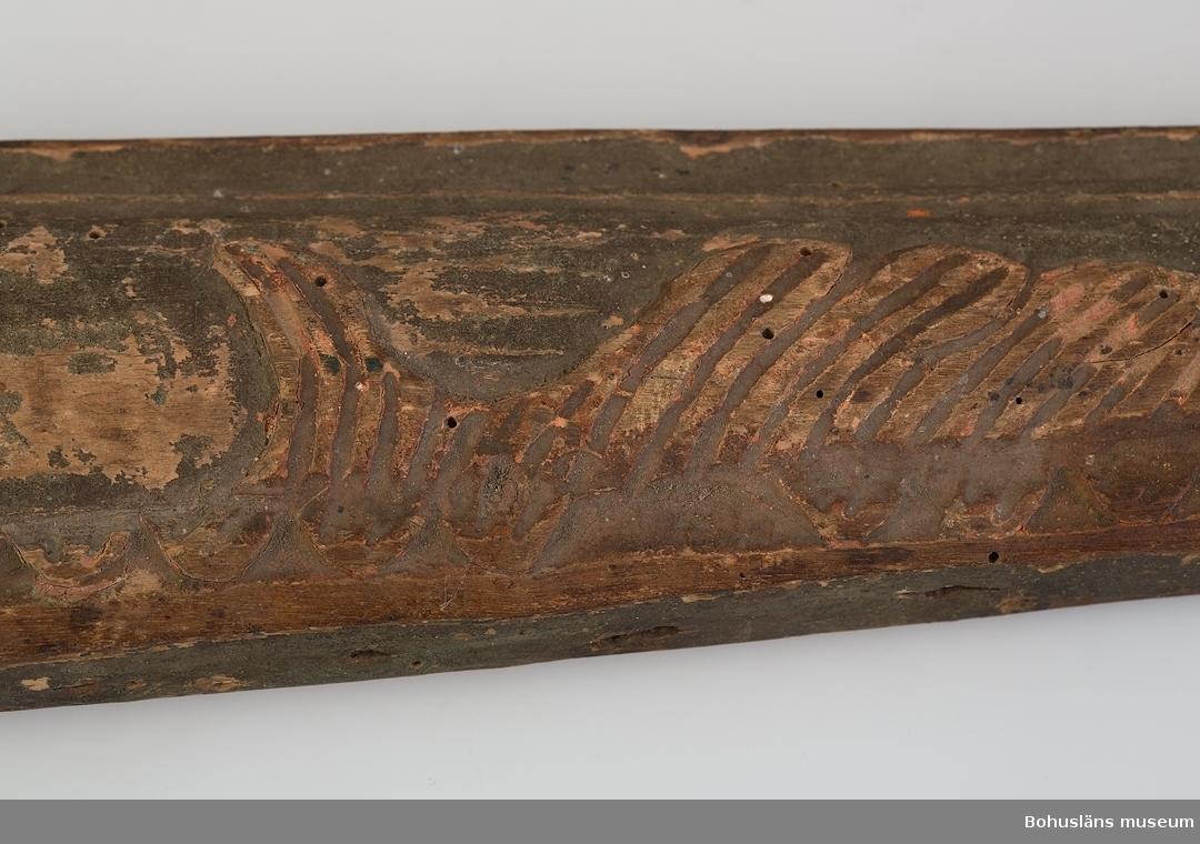 Består av två s-formade trästycken. Ovansidan har skuren dekor i form av rocailleornament och liljor i relief. Rester av röd och grågrön färg. Upptill är de ihopsatta med en järnring. På utsidorna är ett järnbeslag att fästa de lösa skaklarna i. Nertill är smidda beslag att spänna fast bogträet med. På insidan är en rad av spikhål efter stoppning (tagel täckt med läder). Lagning upptill på vänster bogträ. Skadedjursangrepp.  Litteratur: Edvardsson, Ingmar, Rack, ryss och rissja, Stockholm 1995, s. 66 samt bild s. 42.  Ur handskrivna katalogen 1957-1958: Ett par bogträn L. a) 75,5, b) 75,0 cm; upptill fäst m. järnlänk, järnbeslag, skuren dekor i relief, målade i rött o grönt; stoppn. saknas; trasiga, maskätn.  Lappkatalog: 40 Hugo Hallgren var son till salteriidkaren och handelsmannen Johan Jacob Hallgren och Emelia Gerle. Företaget började sälja brissling på 1850-talet och 1864 startade man konservfabrik på Gullholmen som senare döptes till J. J. Hallgren & Söner. Sönerna var Gustav Richard, f. 1858 och Oscar Hugo, f. 1867.  Här introducerades flera nyheter inom ansjovisindustrin,  bl a Sveriges första skinn- och benfria delikatessill. Företaget var också först med att lägga in ansjovis i hermetiskt slutna kärl av bleckplåt. 1898 köptes Hallgrens konservfabrik upp av det nybildade storföretaget AB Sveriges Förenade Konservfabriker (SFK). 1901 flyttade Hugo Hallgren till Ellös där han startade en ny konservfabrik.  För uppgifter om förvärvet, se UM005155.