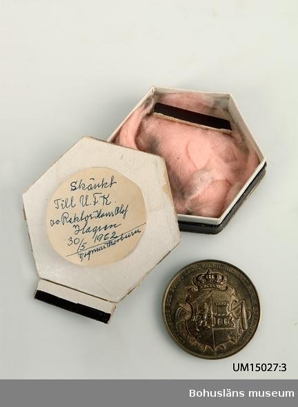 """Formgiven av medaljkonstnärinnan, gravören Lea Ahlborn (1826 - 1897). På framsidan Göteborgs -och Bohus läns vapen under kunglig krona.  Bakom vapenskölden  jordbruksredskap som slaga, räfsa, lie, grephandtag och längst ner ser man underdelen av kärvar. Text runt medaljkanten: """"Göteborgs-och Bohus läns kongl. hushållningssällskap"""".  Med mindre bokstäver signerad """"Lea Ahlborn"""". På åtsidan eklövkrans i relief och inom den graverad text: """"Till Uddevalla Elementarläroverk för flickor"""".  Kring medaljens kant: """"Till minnet af hundraårig verksamhet 1914"""".  På medaljens kant ingraverat: """"Utställningen av handarbeten sommaren 1914"""". Medaljen förvarad i sexkantig ask av mörkt vinröd papp och med text på lockets ovansida i i guldbrons: """"F. Linder juvelerare, Uddevalla"""". Lockets kanter trasiga. (Det finns också en rund utanpå rödfärgad ask, endast bottendelen, märkt med samma nummer. Denna del hittades bland det naturhistoriska materialet med en stor skalbagge förvarad i; februari 2007. Etikett från Bokström Juvelerare Uddevalla, samt handskriven  lapp med texten """"Skänkt till U.F.K av Rektor Hans Olof Hagren 30/5 1962 / Dagmar Thorburn"""".) Gåva från skolan till  Uddevalla flickskolas Kamratförening av flickskolans rektor Hans Olof Hagren. Skänkt vidare till Bohusläns museum av Uddevalla Kamratförening genom styrelsemedlemmarna Gertrud Grenholm och Dagmar Thorburn."""