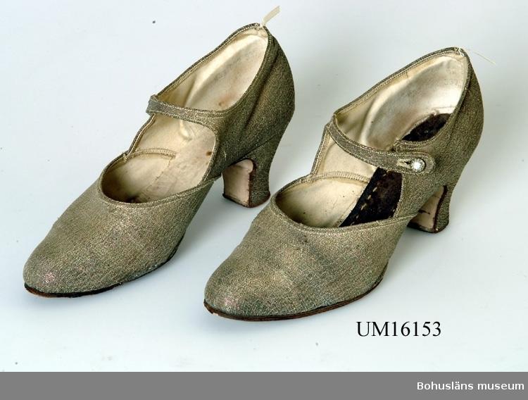 Med sleif och 7cm hög något svängd klack. Storlek 38. Tillverkade av brokadtyg på bomullstvills. Lädersula och läderklack, skimrande i beige, grönt och rosa. Knapp med strass i. Hela, men vänster sko saknar innersula.