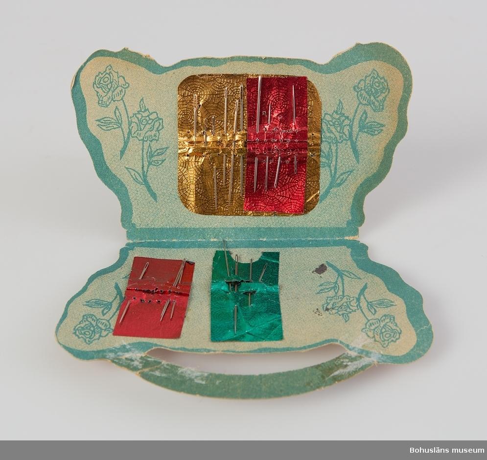 """Dubbelvikt i form av korg med rosor i rött, gult, grönt och brunt. Blå insida med rosor och ursprungligen fyra kartor nålar,en saknas, tillsammans 18 nålar. Ett av """"korgens"""" handtag saknas, ett trasigt."""