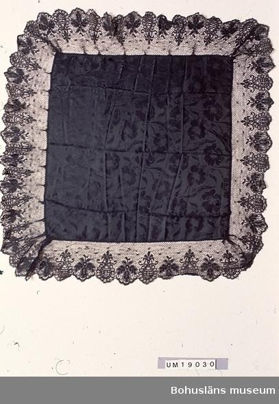 """Jacquardvävd svart sidenschalett mönstrad över hela ytan med ett blommönster. En ca 14 cm bred maskintillverkad spets av bomull är fastsydd ytterst. Kanterna vikta mot rätan och spetsen fastsydd för hand över de vikta kanterna. Använd av Clara Nilsson f 1866 d 1946, mormor till givarna Harriet Hägglund och Birgit Kristiansson. Tillverkningstid utifrån att i slutet av 1860-talet kom raschelmaskinen som gjorde att olika tekniker (såsom botten lik knyppling och mer vävliknande partier) kunde kombineras i samma spets. Osäkert under vilka år schaletten är använd. Bristningar och mycket små hål i tyget framförallt på ena halvan av schaletten. Spetsens ytterkant sliten.  Litt; Håkansson, Elin, Sidenhalsdukens bruk och tillverkning ur """"Sörmlandsbygden"""" 1933. Lewis, Katarina, Schartauansk Kvinnofromhet i tjugonde seklet, Uddevalla 1997, sid. 126. Lindvall-Nordin, Christina, Mossrosor och hjärtblomster ur Kulturens årsbok 1969, Lund. Wulfcrona-Dagel, Marie Louise, Schaletter och halskläden i Nordiska museet vävda hos K A Almgrens sidenväveri i Stockholm, uppsats för fortsättningskurs i etnologi, Stockholm 1979. Omkatalogiserat 1997-05-12"""