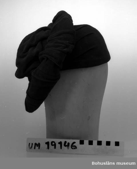471 Tillverkningstid 1940-TAL 410 Mått/Vikt ! BRÄTTB. 7 CM 394 Landskap BOHUSLÄN  Damhatt i mörkblå velour med brätten och liten kulle. Nerdraget nackparti.  Brätten har nerstickade draperingar av tyget. Taftfodrad.   Se UM19130.