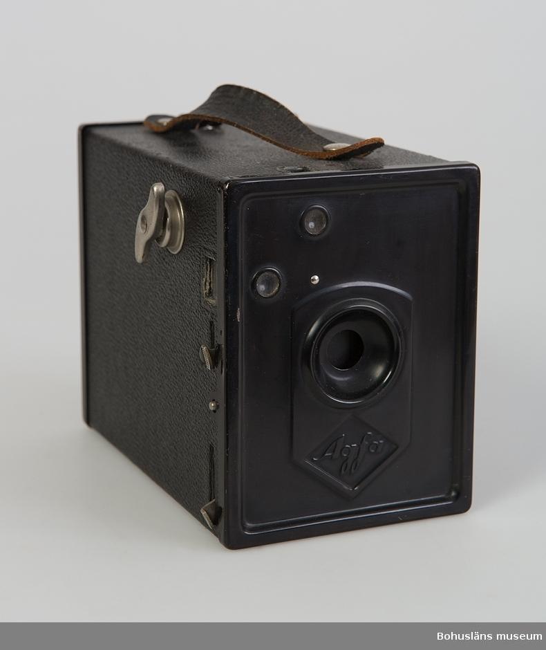 """Lådkamera, svart, delvis klädd med präglat målat papper som ska likna läder (läderimitation). Handtag av läder. Märke: AGFA. För rullfilm 6x9 cm. Präglat i papperet på kamerans undersida: MADE IN GERMANY. På bakstyckets insida finns en fastklistrad glansig bild i färg, en avbildad filmrulleförpackning och texten """"Agfa Isochrom B2 * 6X9 cm"""". Troligen är kameran en Agfa Box Nr. 44 B2 6x9, som tillverkades från 1932. (Uppgiften hämtad från Internet i juni 2004.)   Från insamling av föremål från vindskontor över Antonssons Livs m.m., kvarter Ridhuset , Södra Drottningg.12 (rivningsfastighet), Uddevalla."""