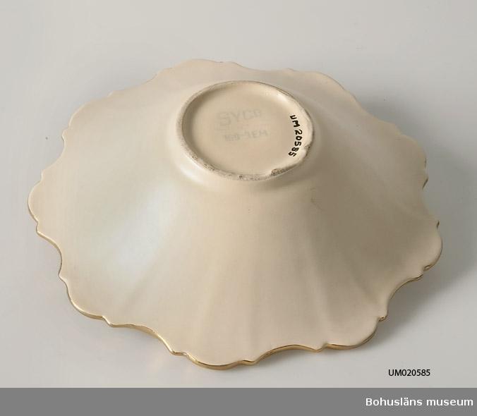 """Halvsfärisk skål med utåtböjd kant. Beige färgad glasyr.  Märkt i botten med tryckt, blå signatur: """"SYCO Made in Sweden 169-3 EM."""""""