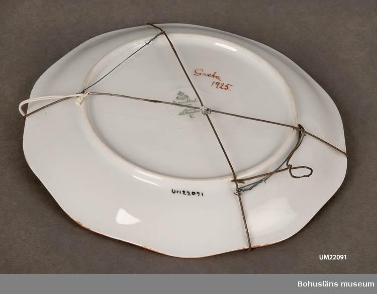 """594 Landskap BOHUSLÄN  """"Rosenthal Bavaria modell PH Rosenthal. E."""" Pärlstavsmönster på brämet. Kanten brunmålad. Handmålade fantasiblomster i spegeln. Undersidan märkt:""""Greta 1925."""" Fatet försett med upphängningsanordning av järntråd.  UMFF 76:2"""