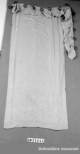 410 Mått/Vikt ! Draperi: L 195, B 80 cm. Kappa: L 20, B 200 cm. 594 Landskap BOHUSLÄN  Kappa med 14 träringar fastnästa vid draperi och kappa. Ljusbrun.  UMFF 115:4