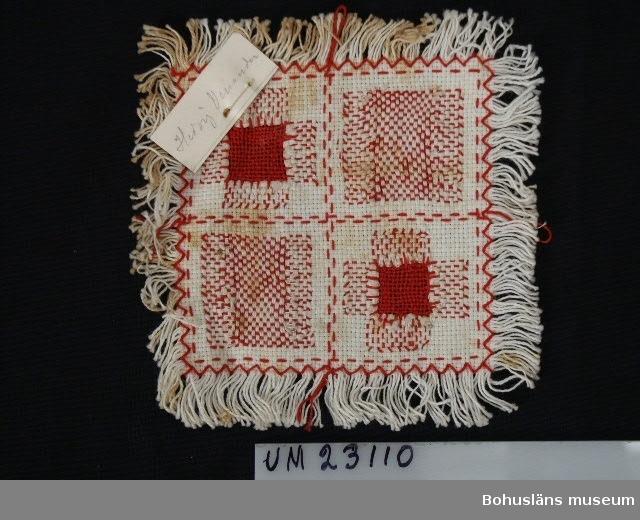 594 Landskap BOHUSLÄN 503 Kön KVINNA 394 Landskap BOHUSLÄN  Stycke med olika typer av stoppar och lagningar i textilier. Skolslöjdsarbete.  Rött och vitt för att lagning skulle kunna ses och bedömas.
