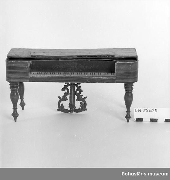 594 Landskap BOHUSLÄN  Klaver i nyrokoko. Fyra rikt svarvade ben. Pedalhållare i bly, brunmålad och rik nyrokokodekor. Klaviatur i form av tryckt papper med tangenter. Resonanslåda klädd med papper med dekor av ädelträfaner.  Neg. nr UM 148:9