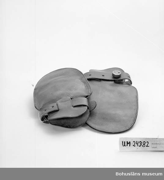 Saknar tummar. Tjockt läder. Slitna. Läderrem runt handleden vilken kan dras åt.  Runt metallås vid remmen. Dessa användes när en patient ville riva och klösa sig själv eller andra eller inventarier. Skomakaren på sjukhuset har tillverkat sådana här, men det är inte säkert att han tillverkat dessa.
