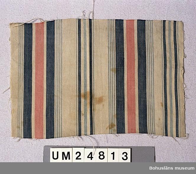 Varpen randig i blått, ljusblått, vitt och ljust blåtonat rött (rosa). Färgerna troligen indigo och koschenill. Inslaget enfärgat vitt. Insamlat av Berta Kleberg. Bruna fläckar. Ytterligare uppgifter om gåvan UM24798 - UM24883, se UM24798.