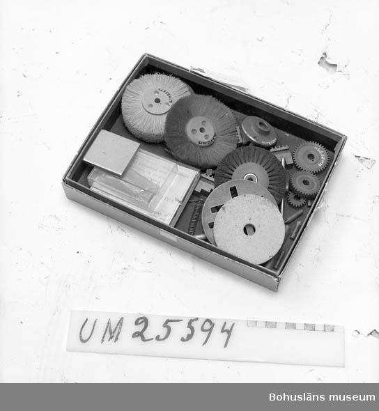 594 Landskap BOHUSLÄN  Papplåda (urspr.för fotopapper) innehållande reservdelar och extradelar till svarv UM25572, polerborstar, kugghjul m.m.  Ytterligare uppgifter om Åke Seinknecht och hans ljudsamling se UM25572.